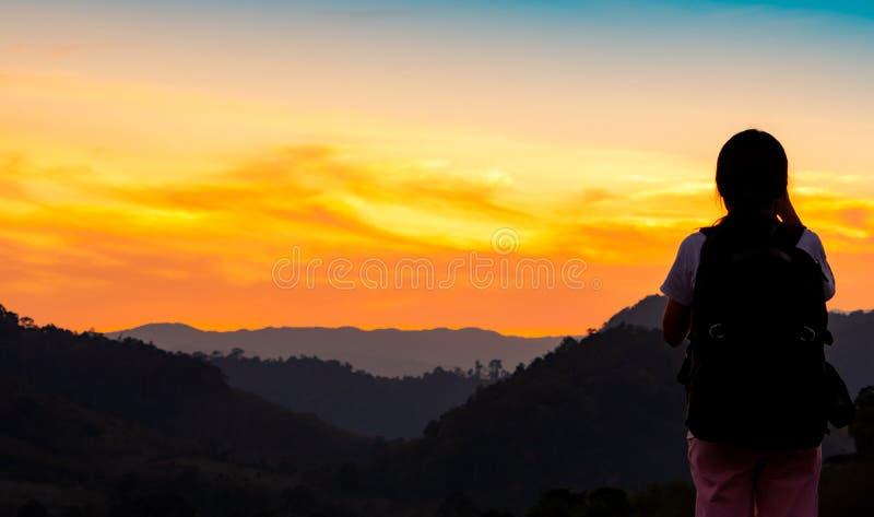 Opinión trasera la mujer joven que mira puesta del sol hermosa sobre capa de la montaña Backpacker feliz en viajar solamente Si foto de archivo