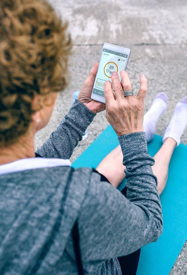 Opinión trasera la mujer mayor que usa smartphone fotografía de archivo