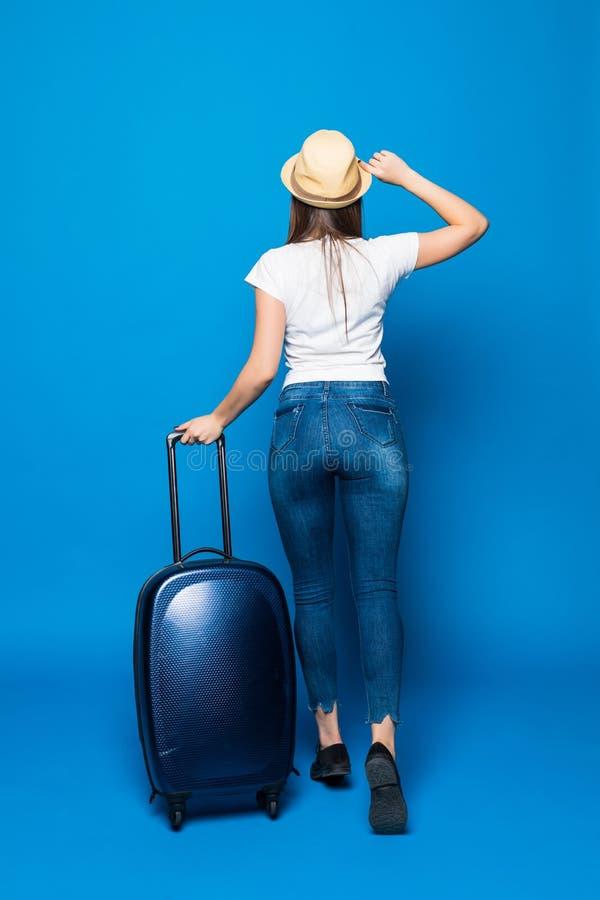 Opinión trasera la mujer que camina con la maleta Muchacha hermosa en el movimiento opinión de la parte trasera el viajero con el foto de archivo libre de regalías