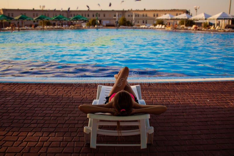 Opini?n trasera la mujer que miente en ocioso cerca de piscina en el hotel, tiempo de verano del concepto imagen de archivo libre de regalías