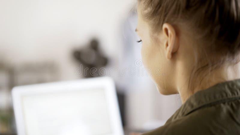 Opinión trasera la mujer que trabaja con un ordenador portátil imagenes de archivo