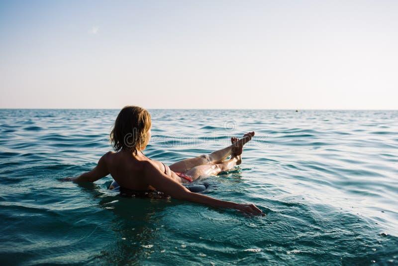 Opinión trasera la mujer relajante que flota en el anillo inflable imagen de archivo libre de regalías