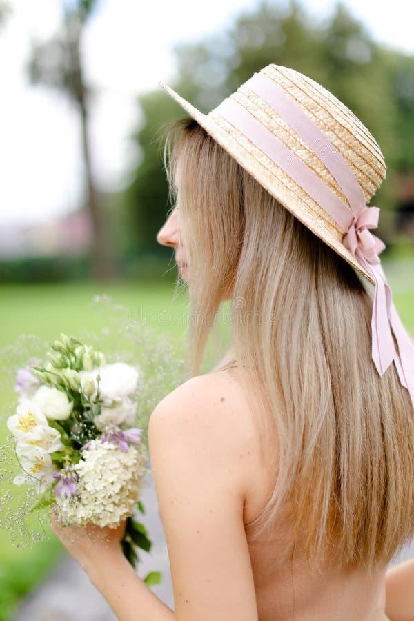 Opinión trasera la mujer rubia joven en guardapolvos y sombrero del color de cuerpo con las flores foto de archivo