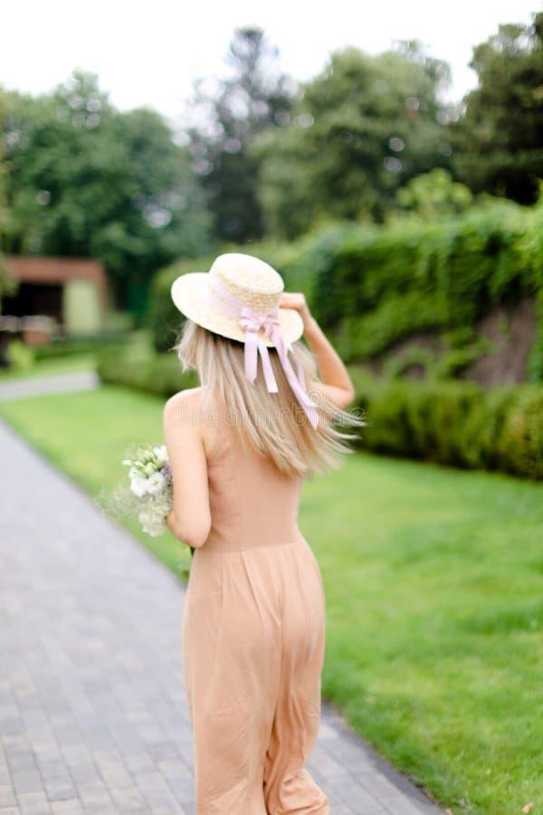 Opinión trasera la mujer rubia joven en guardapolvos y sombrero del color de cuerpo imagenes de archivo