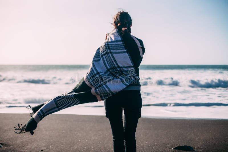 Opinión trasera la mujer sola joven que goza del océano fotografía de archivo