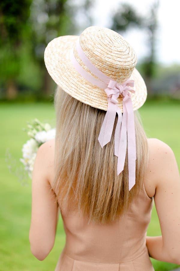 Opinión trasera la persona femenina joven en guardapolvos y sombrero del color de cuerpo imagenes de archivo