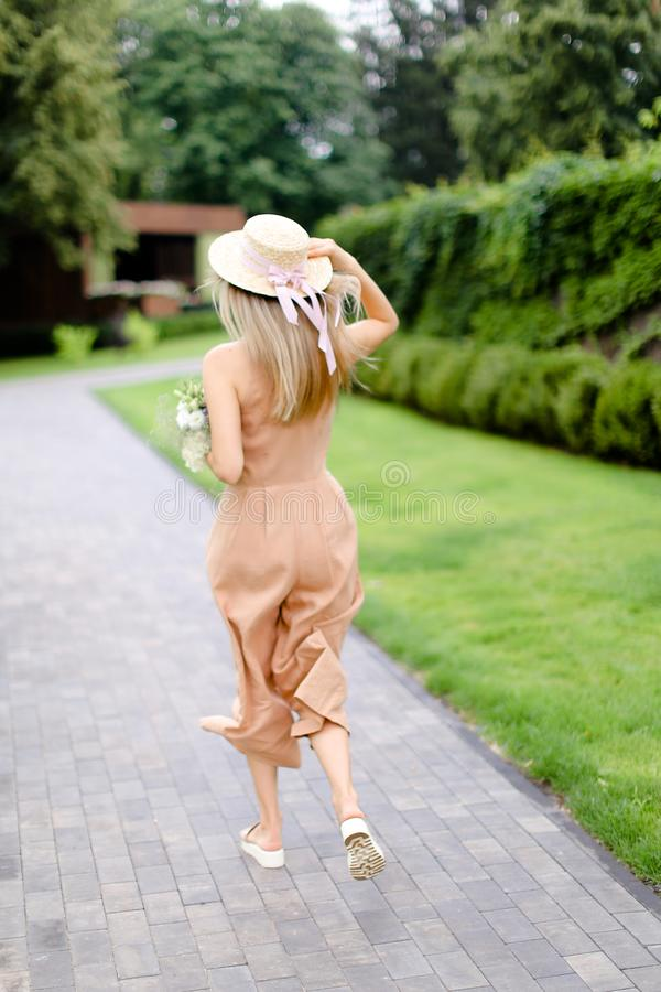 Opinión trasera la persona femenina rubia joven en guardapolvos y sombrero del color de cuerpo con las flores fotos de archivo