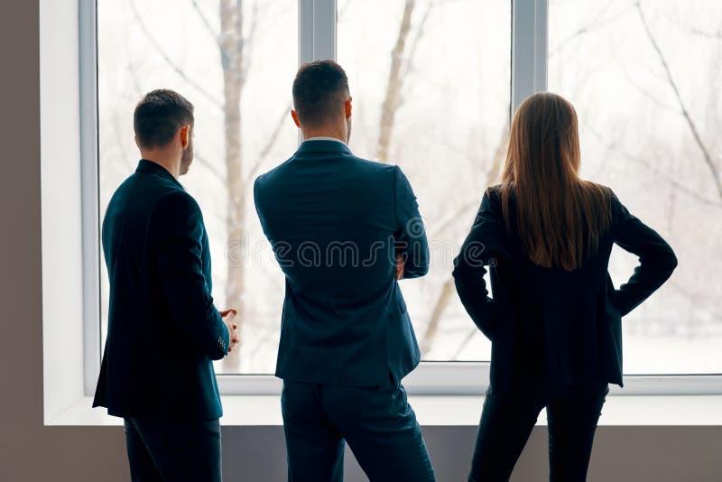 Opinión trasera los hombres de negocios que hablan durante el soporte del descanso para tomar café cerca de la ventana en oficina fotografía de archivo libre de regalías