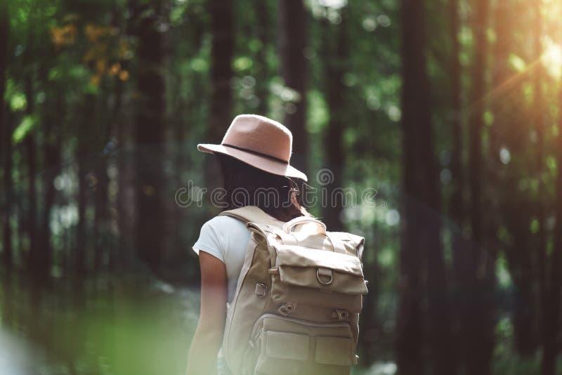 Opinión trasera sobre la mochila del viajero y el sombrero que lleva de la muchacha del inconformista Los jóvenes hacen frente a  foto de archivo libre de regalías