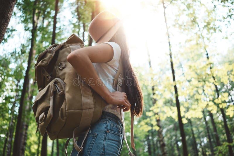 Opinión trasera sobre la mochila del viajero y el sombrero que lleva de la muchacha del inconformista Los jóvenes hacen frente a  imagenes de archivo