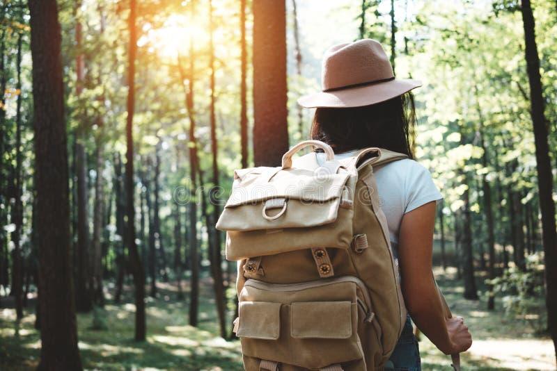 Opinión trasera sobre la muchacha hermosa del inconformista del viajero con la mochila y el sombrero que camina en bosque entre á imagen de archivo