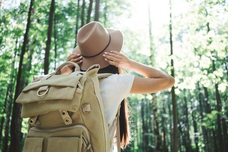 Opinión trasera sobre la muchacha hermosa del inconformista del viajero con la mochila y el sombrero que camina en bosque entre á fotos de archivo