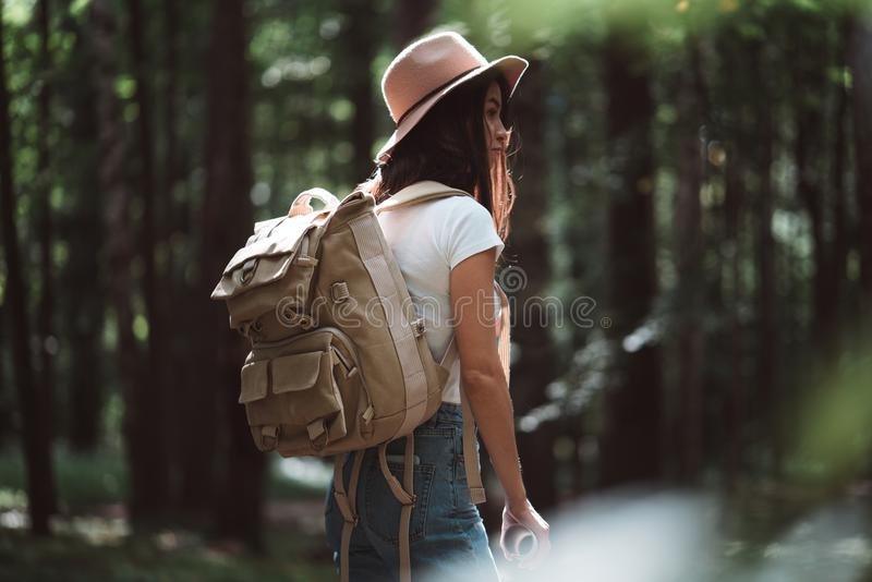 Opinión trasera sobre mujer joven linda con el sombrero, la mochila y el mapa de ubicación a disposición entre árboles en bosque  imágenes de archivo libres de regalías