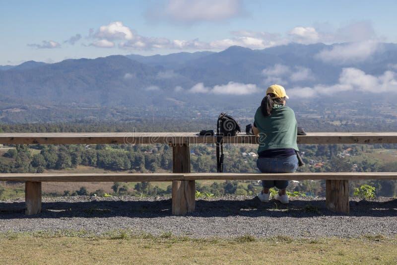Opinión trasera solamente de la mujer joven que localiza en banco de madera largo y que mira el fondo de la montaña y del cielo a fotografía de archivo