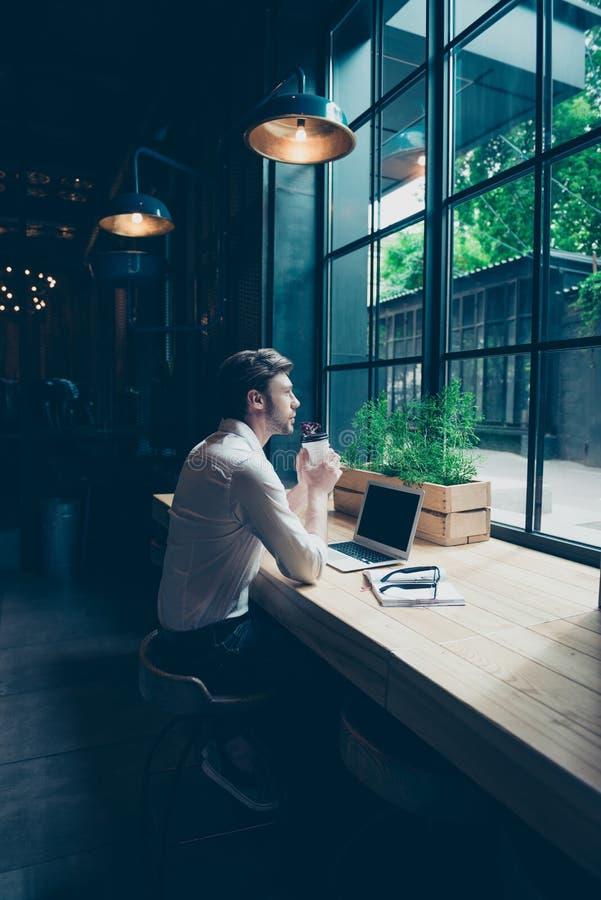 Opinión trasera un empresario, sentándose en el restaur moderno oscuro fotografía de archivo