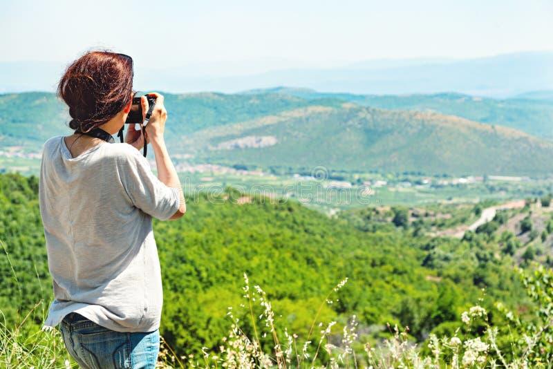 Opinión trasera un fotógrafo de la mujer que toma las imágenes del valle con las montañas desde arriba imagenes de archivo