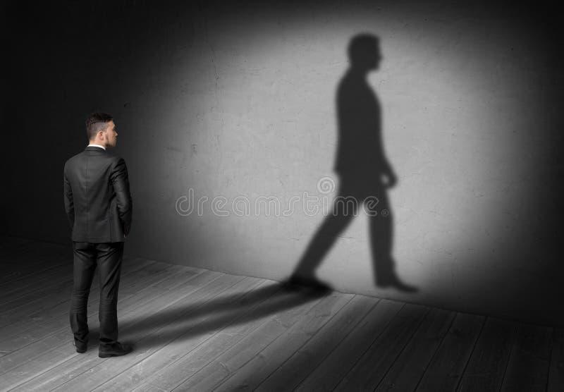 Opinión trasera un hombre de negocios que mira su sombra que camina en la pared imagenes de archivo