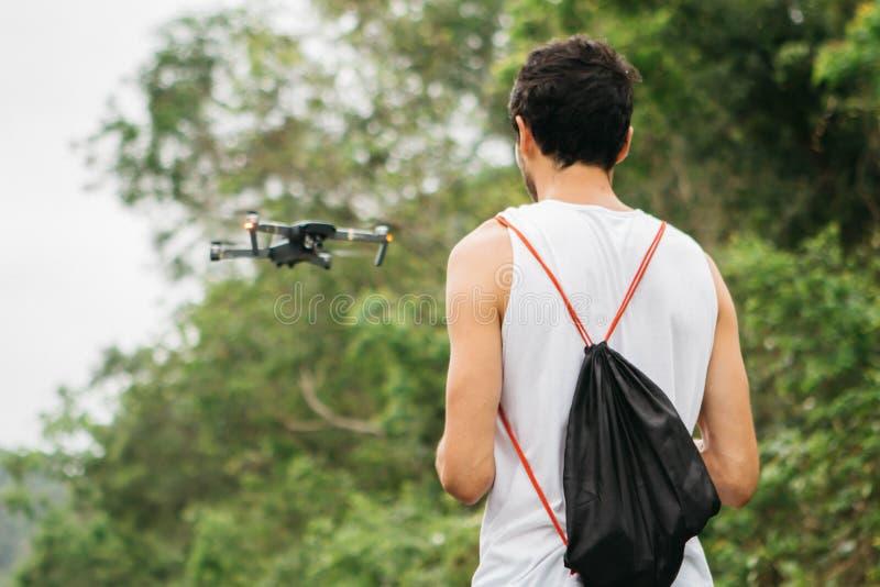 Opinión trasera un hombre joven que actúa un abejón por teledirigido en el parque fotos de archivo