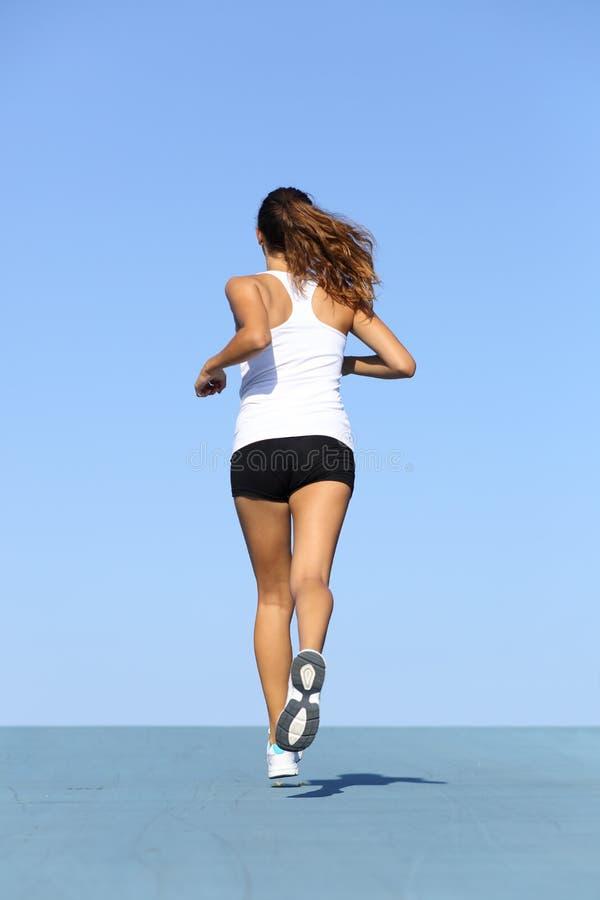 Opinión trasera una mujer de la aptitud que corre en azul fotos de archivo