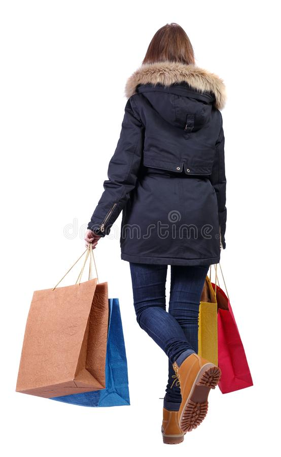 Opinión trasera una mujer en una chaqueta del invierno que viene con los bolsos que hacen compras de papel fotos de archivo libres de regalías