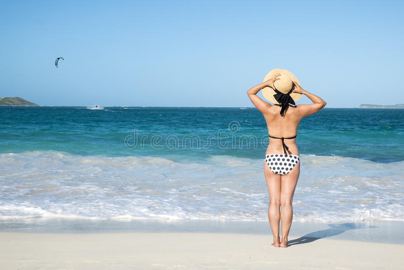 Opinión trasera una mujer en la polca Dot Bikini Standing en una playa 1 imagen de archivo libre de regalías