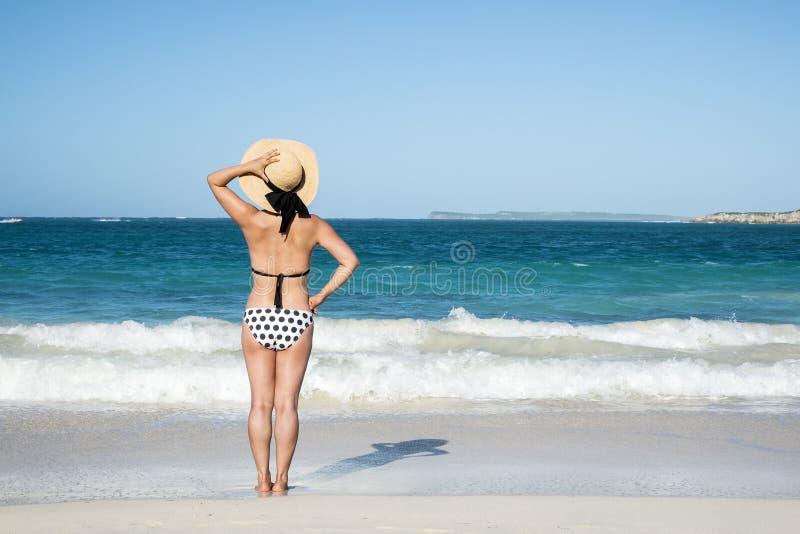 Opinión trasera una mujer en la polca Dot Bikini Standing en una playa 2 fotos de archivo libres de regalías