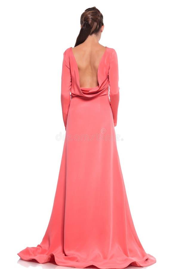 Opinión trasera una mujer en un vestido rosado con la parte posterior desnuda imagenes de archivo