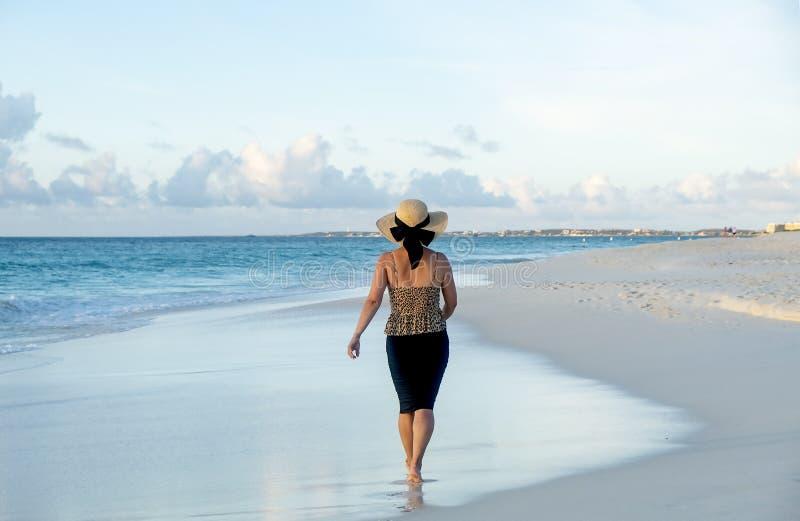 Opinión trasera una mujer que camina descalzo en una playa del Caribe 4 imagenes de archivo