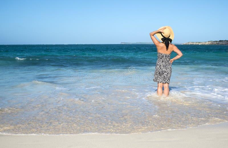 Opinión trasera una mujer que se coloca en la playa 3 imagen de archivo