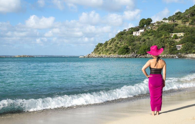 Opinión trasera una mujer que se coloca en la playa 1 fotografía de archivo