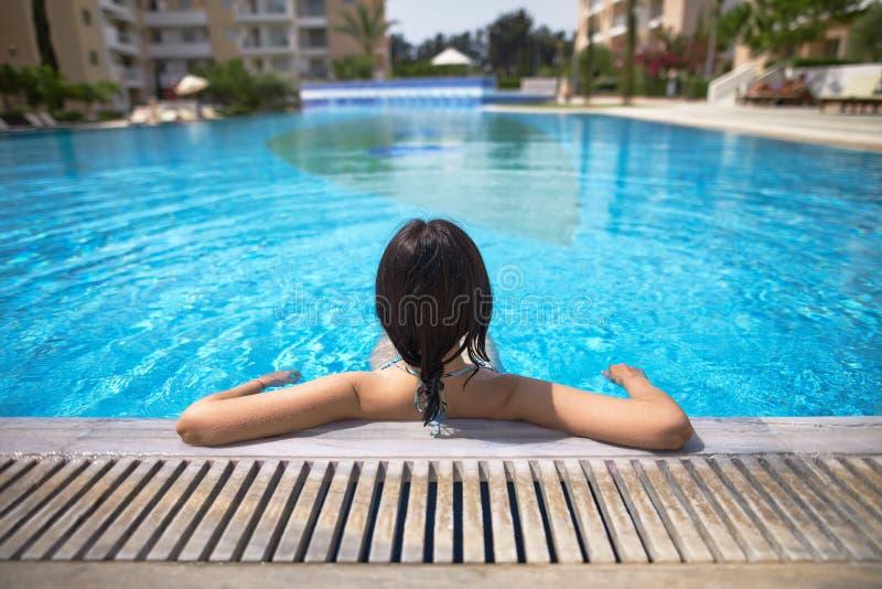 Opinión trasera una mujer que se relaja en piscina fotos de archivo libres de regalías