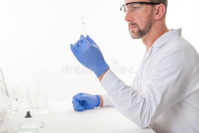 Opinión un hombre en el laboratorio mientras que experimenta la ejecución foto de archivo libre de regalías
