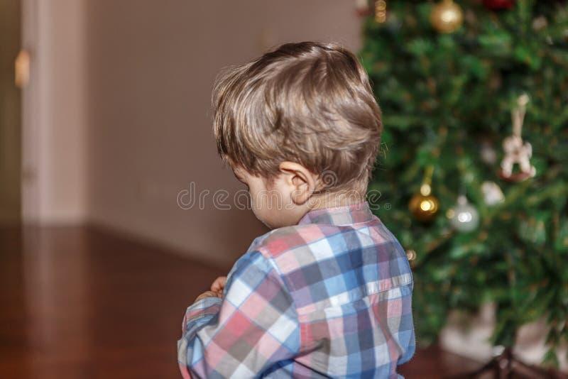 Opinión un niño pequeño cerca de un árbol de navidad adornado imágenes de archivo libres de regalías