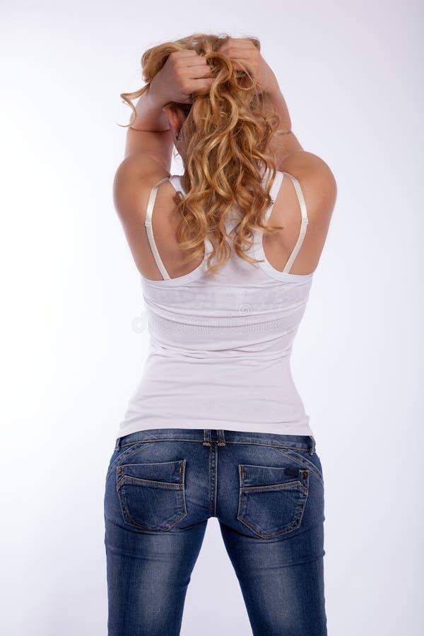 Opinión una mujer rubia en un top blanco y tejanos imagen de archivo libre de regalías