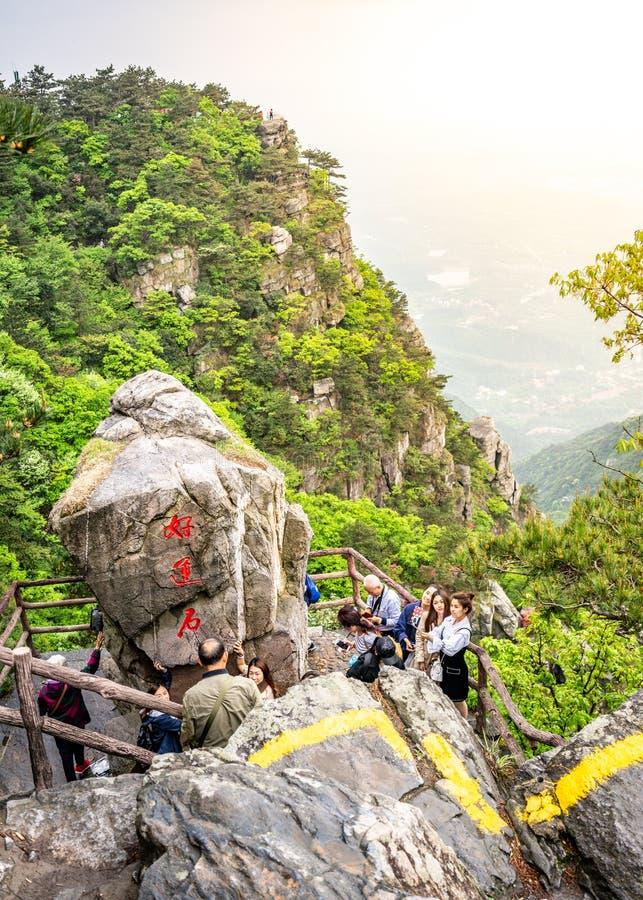 Opinión vertical los turistas chinos que presentan al lado de una roca grande en parque nacional de la montaña de Lushan en el so fotografía de archivo