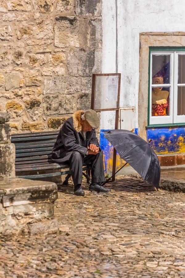 Opini?n ancianos con la capa t?pica, sent?ndose en banco de madera, con el sombrero de la lluvia abierto en la tierra, en el cuad fotografía de archivo