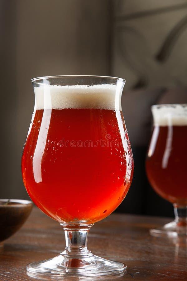 Opini?n ascendente cercana sobre la cerveza ambarina fr?a en un vidrio con bocado en la barra en la tabla Cocnept de la imagen de imágenes de archivo libres de regalías