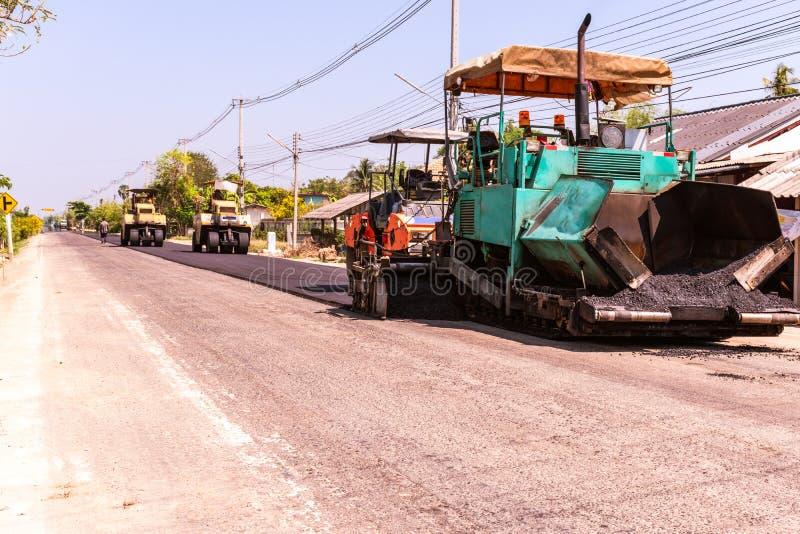 Opini?n cercana sobre los trabajadores y las m?quinas de asfaltado, trabajadores que hacen el asfalto en la construcci?n de carre imagenes de archivo