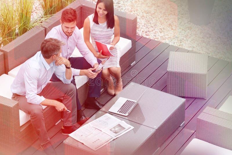 Opini?n de alto ?ngulo colegas con la tecnolog?a que se sienta en la terraza de la oficina foto de archivo libre de regalías
