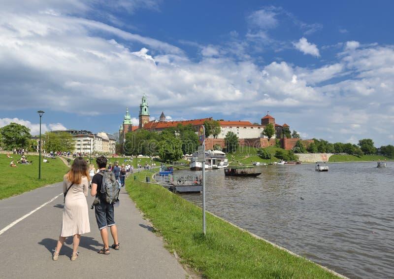 Opini?n de la primavera sobre el castillo de Wawel, el r?o Vistula, el parque de la primavera, el carril de bicicleta y turistas  imágenes de archivo libres de regalías