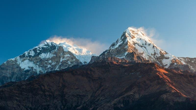 Opini?n de Poonhill de Annapurnas Rosa caliente y luz anaranjada de la salida del sol sobre la cordillera de Annapurna con el cie fotos de archivo