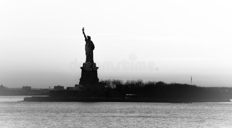 Opini?n del contraluz de la estatua americana del s?mbolo de la silueta de la libertad en Nueva York, los E.E.U.U. Alta imagen bl fotos de archivo libres de regalías