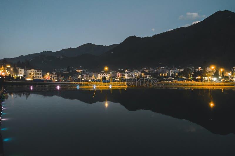 Opini?n del paisaje de la ciudad de la noche con el fondo de la monta?a y reflexi?n del cielo nublado en el agua situada en SAPA, imágenes de archivo libres de regalías