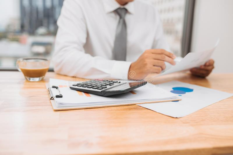 Opini?n parcial el hombre de negocios con el funcionamiento de la calculadora en el lugar de trabajo con los documentos y el orde imagen de archivo