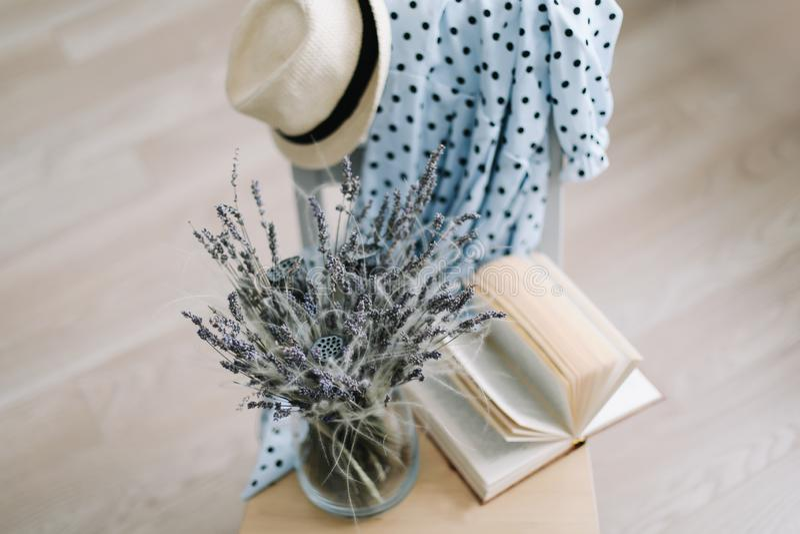 Opini?n superior de la endecha plana creativa Vestido azul, sombrero del verano, flores en un florero y un libro en fondo de made imagen de archivo