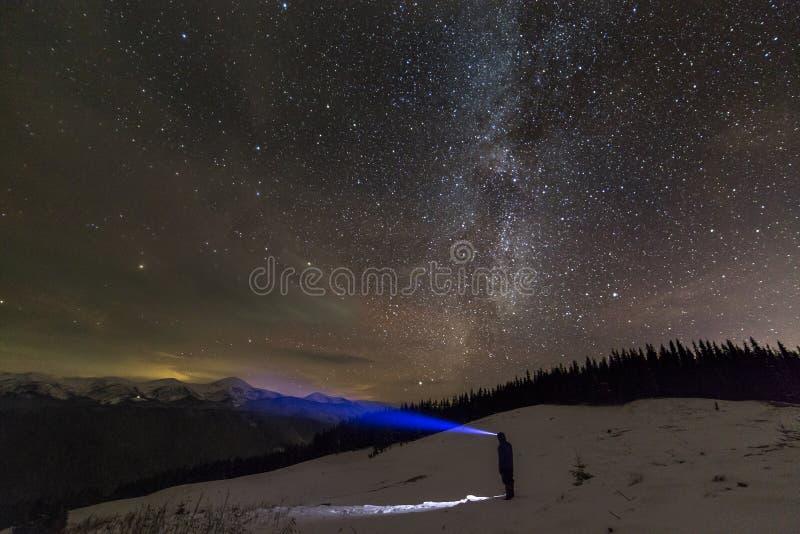 Opini?n trasera el hombre con la situaci?n principal de la linterna en el valle nevoso debajo del cielo estrellado del invierno a imagen de archivo