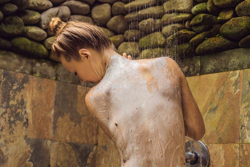 Opini?n trasera la mujer joven desnuda hermosa que toma la ducha en cuarto de ba?o imagen de archivo