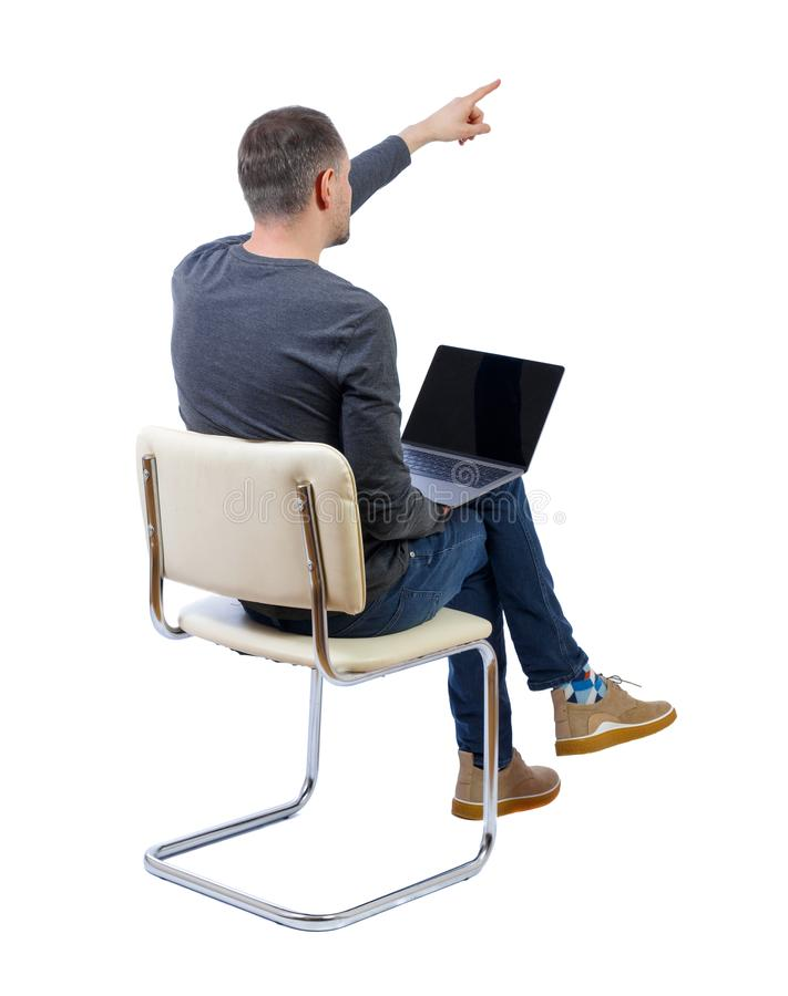 Opini?n trasera un hombre que se sienta en una silla con un ordenador port?til y puntos con su mano adelante foto de archivo