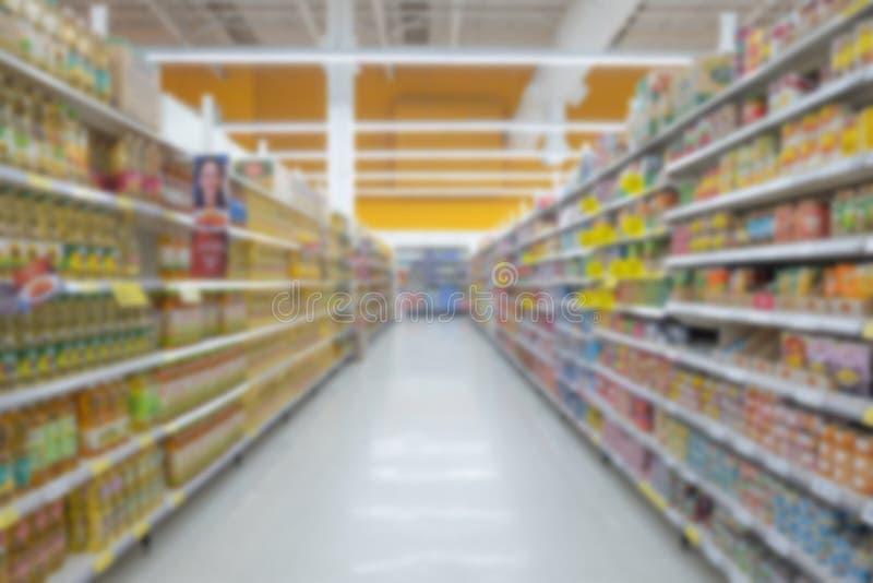 Opini?o borrada abstrata do supermercado do corredor vazio do supermercado, fundo obscuro defocused com luz do bokeh na loja Neg? foto de stock