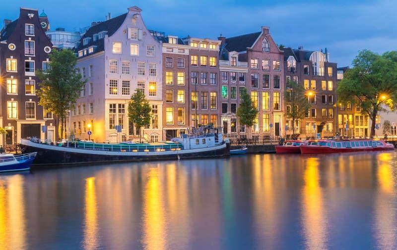 Opini?o da cidade da noite do canal de Amsterd?o, de casas holandesas t?picas e de barcos, Holanda, Pa?ses Baixos foto de stock royalty free